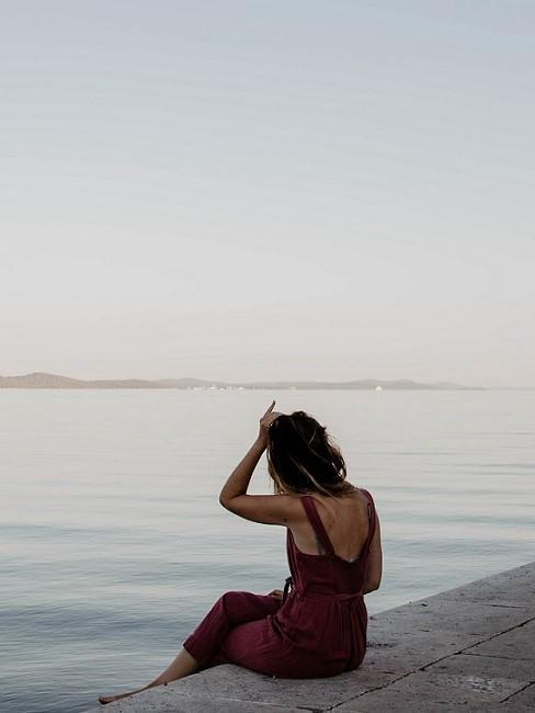 Frau am Meer sitzend und aufs Meer schauend