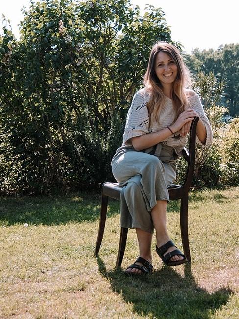 Frau auf Stuhl sitzend im Garten