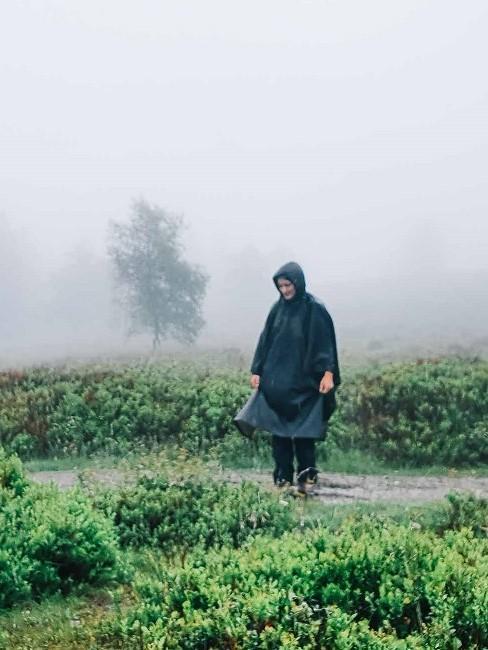 Frau im Nebel mit Regenmantel