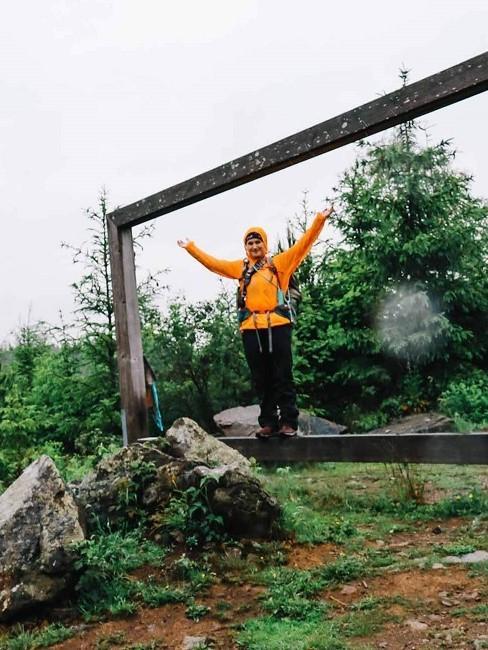 Frau im regnerischen Wald mit orangener Jacke