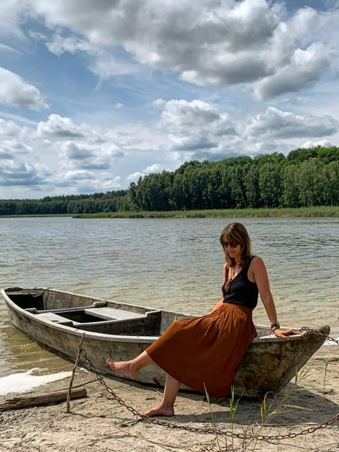 Frau auf Boot sitzend am See