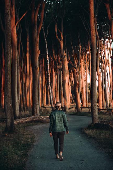 Frau zwischen vielen Bäumen im Wald