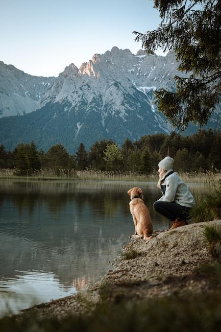 Frau mit Hund am Wasser sitzend
