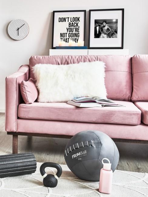 Sitzball für Fitnessübungen liegt im Wohnzimmer vor rosa Sofa