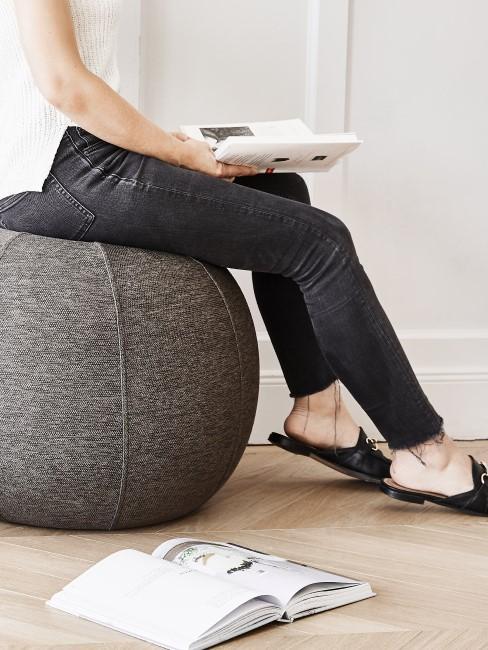Frau sitzt auf einem grauen Sitzball
