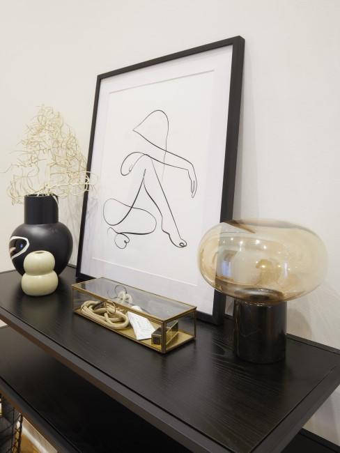 Dunkle Marmor Tischlampe auf Sideboard neben großem Bilderrahmen und Vasen