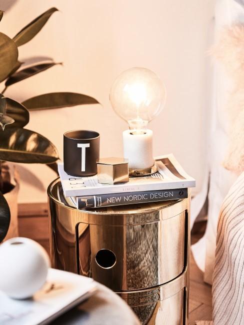 Weiße Marmor Leuchte steht auf einem goldenen Nachttisch neben einer Design Letter Tasse