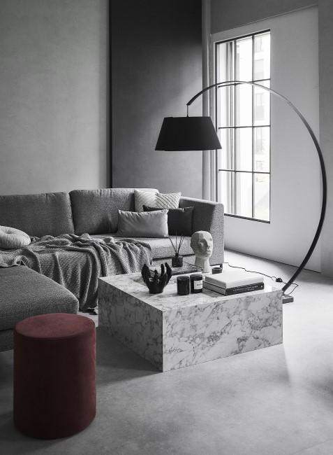 Schwarze Bogenlampe in dunklem Wohnzimmer mit Marmortisch