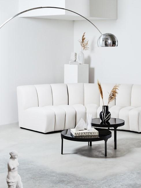 Silberne Bogenlampe in monochromem Wohnzimmer