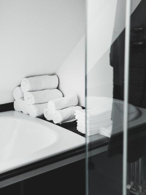 Handtücher liegen auf dem Rand einer schwarzen Badewanne