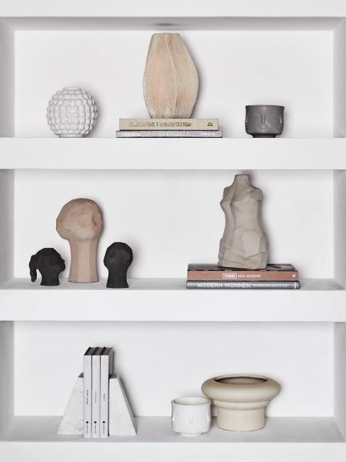 In einem Regal stehen mehrere Deko Köpfe, Vasen und Büsten