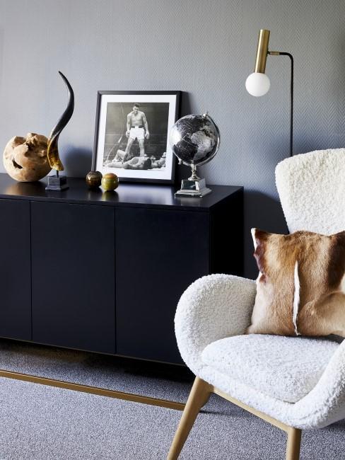Sideboard in schwarz mit Deko-Elementen drauf und ein weißer Sessel