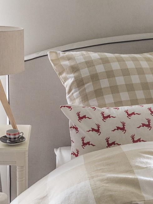 Bettdecke in beige sowie Kissen mit Hirschmotiv