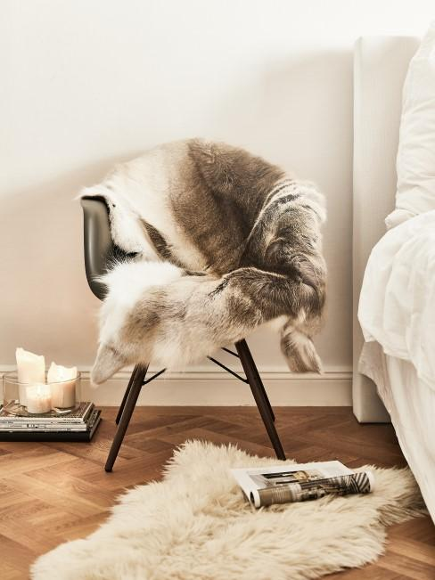 Decke aus Fell auf einem Stuhl und Fellteppich auf dem Boden