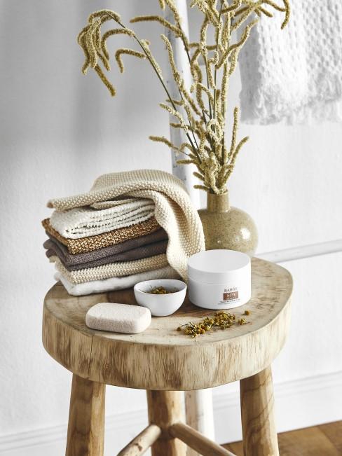 Hocker im Bad aus Holz mit Handtüchern und Accessoires drauf