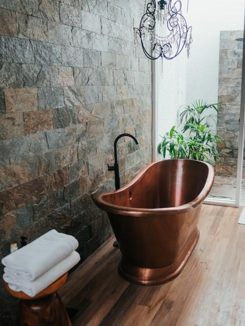 Holzboden im Badezimmer mit kupferfarbener Badewanne