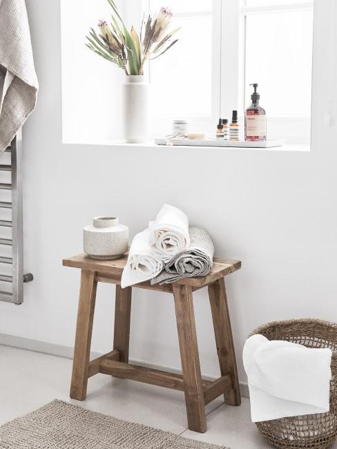 Hocker mit Handtüchern steht in einem hellen Badezimmer