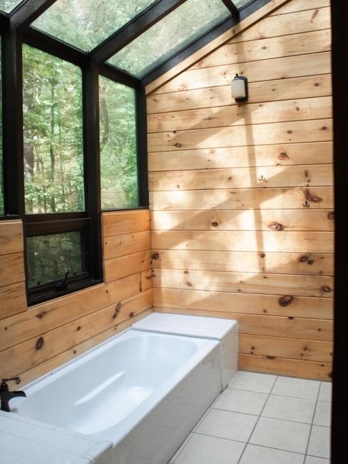 Weiße Badewanne und Holzwände sowie eine gläserne Decke