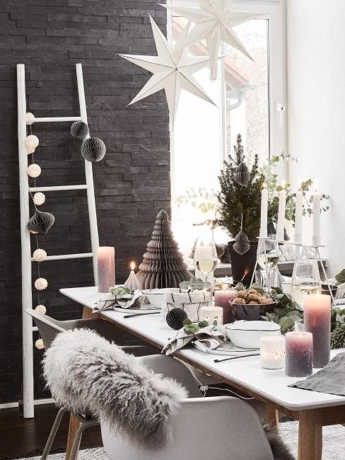Weiße Holzleiter ist weihnachtlich dekoriert und lehnt an einer schwarzen Wand