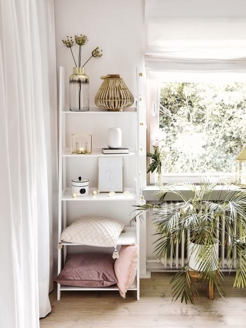 Ein dekoratives weißes Leiterregal steht neben einer Pflanze