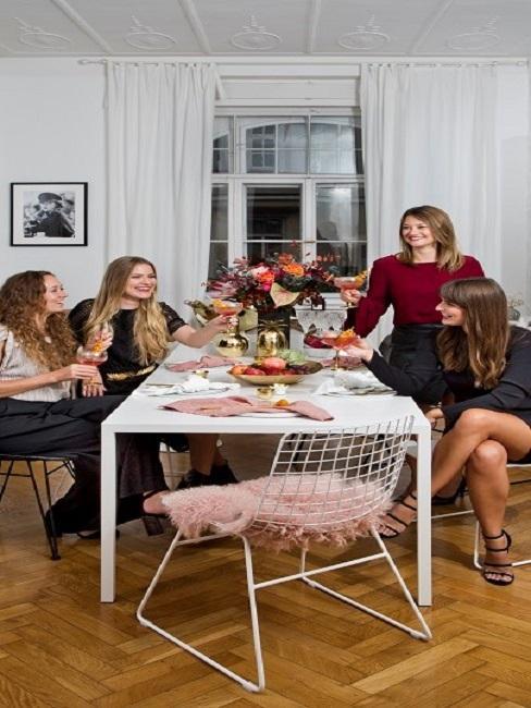 Vier Frauen an einem Tisch, anstoßend