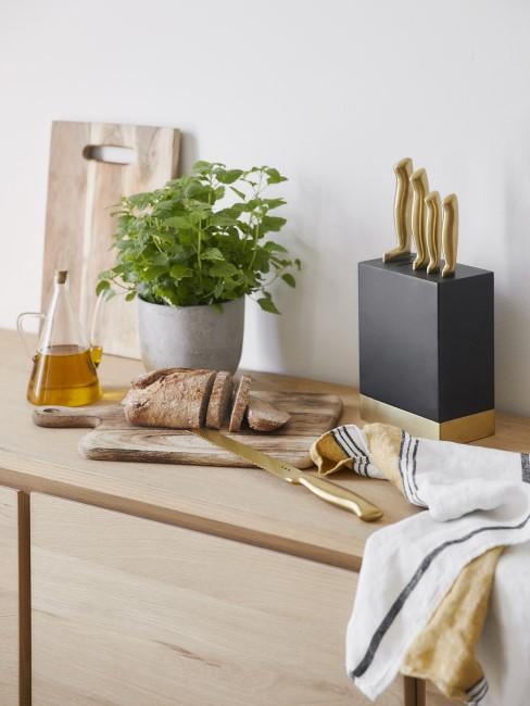 Auf der Arbeitsplatte aus hellbraunem Holz liegt ein Schneidebrett und andere Küchenaccessoires