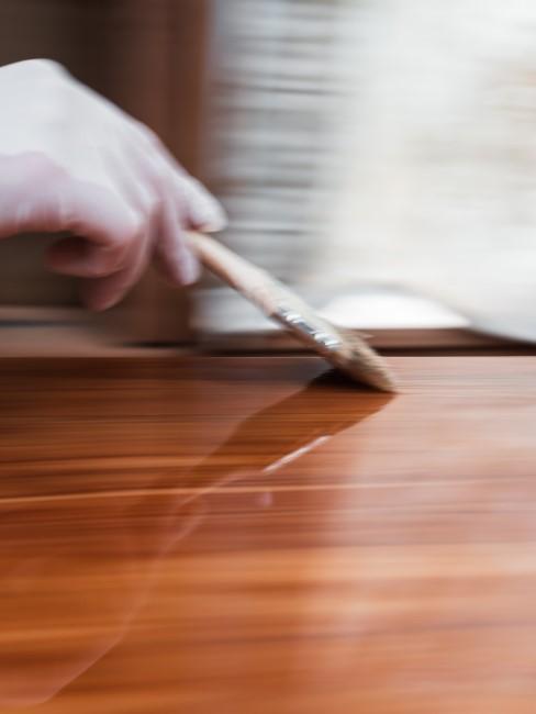 Person nutzt einen Pinsel zum Holz beizen