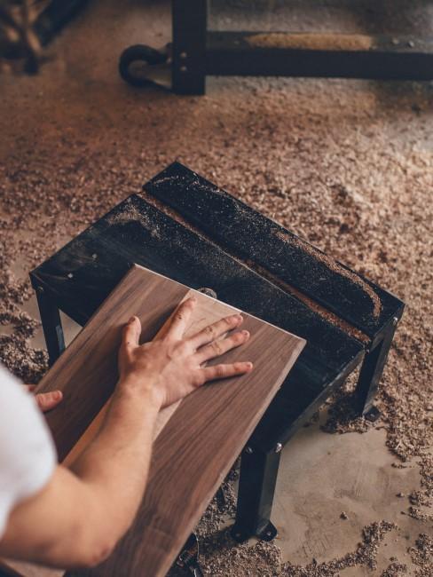 Person bearbeitet eine Holzplatte