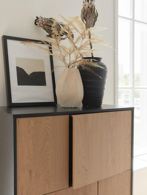 Kommode aus hellem Holz mit Vasen darauf