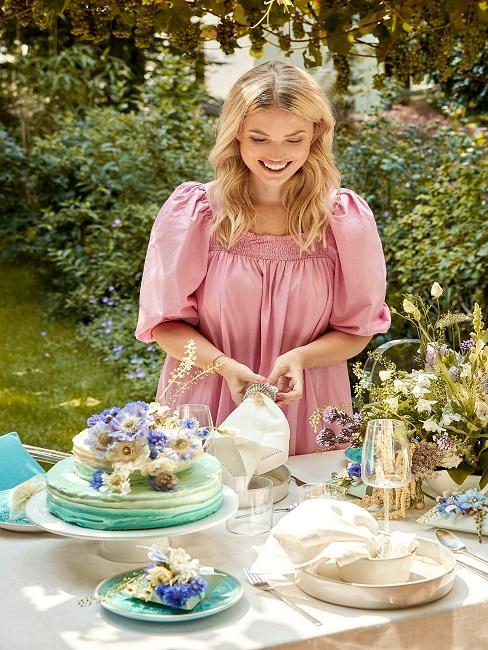 Frau dekoriert Tisch mit Blumen