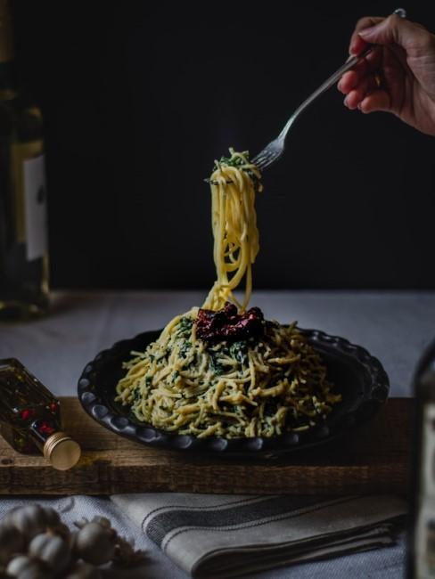 Spaghetti sind auf einem schwarzen Teller angerichtet