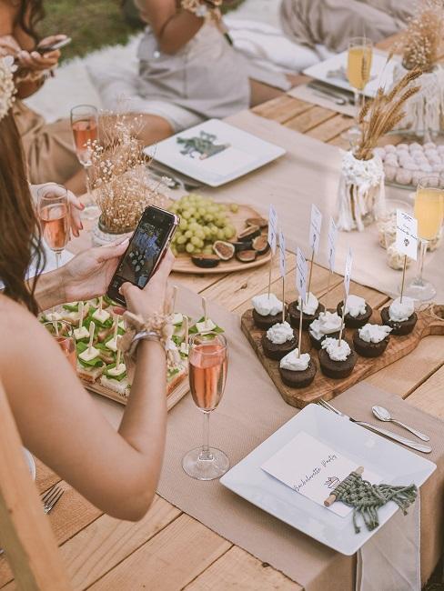 Menschen die um einen Tisch mit Snacks sitzen
