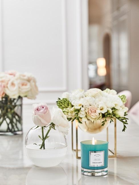Duftkerze mit Blumen in Vasen