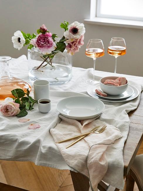 Tischdeko mit Weingläsern und einem Blumenstrauß