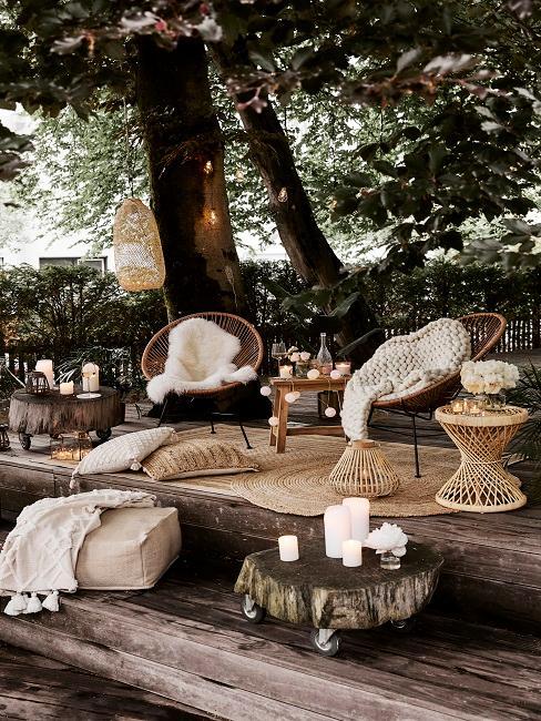 Sessel, Outdoor-Teppich und Beistelltisch in einem grünen Außenbereich
