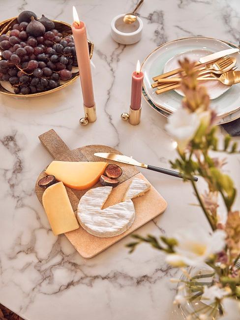 Käseplatte und Trauben auf einem Marmortisch