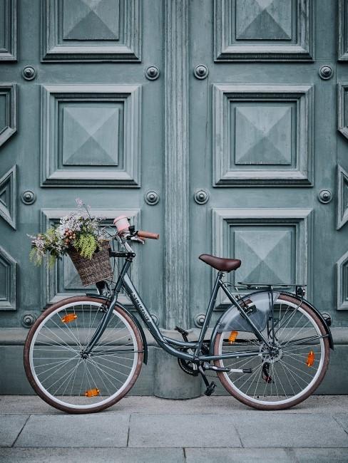 Ein Fahrrad mit Blumen im Fahrradkorb steht vor einer Tür