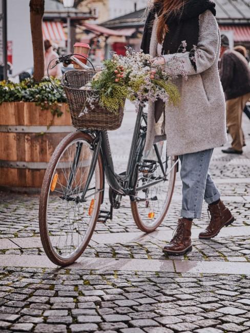 Frau geht mit einem Fahrrad mit Blumen durch die Stadt