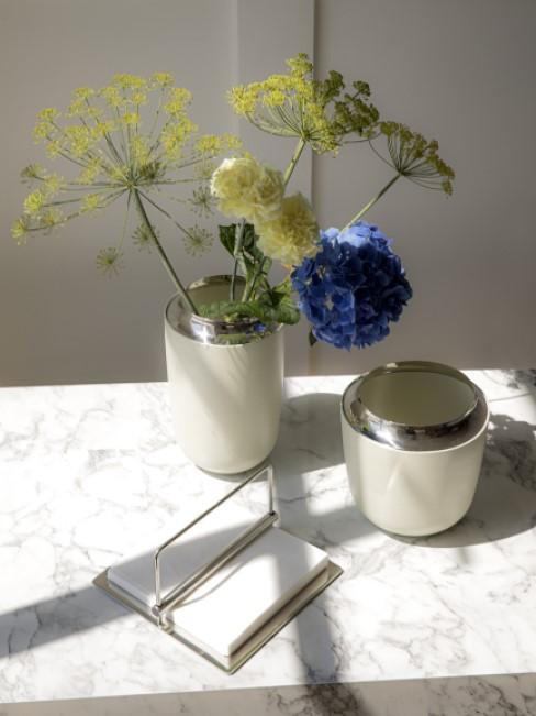 Gelbe und blaue Frühlingsblumen auf einem Marmortisch