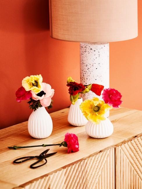 Kleine Vasen mit bunten Ranunkeln auf einer Holzkommode