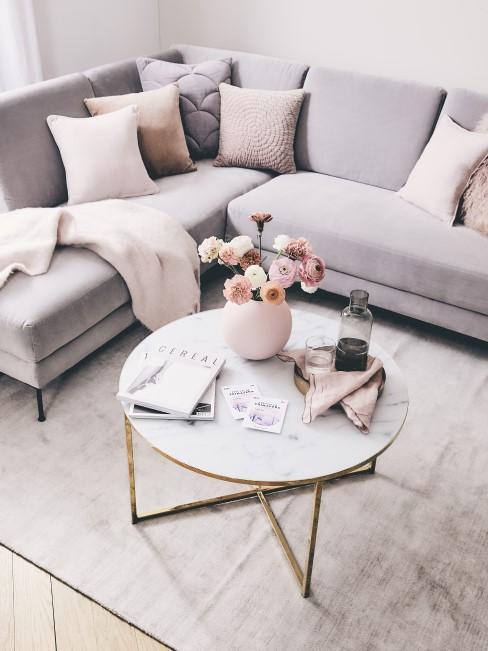 Wohnzimmer in hellen Farben mit Couchtisch im Marmorlook