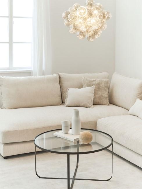 Hell eingerichtete Wohnung mit beiger Couch und Glastisch
