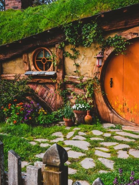 Ein bewachsenes Gartenhaus mit runder Tür