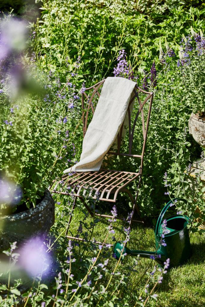 Ein Stuhl steht im grünem Garten