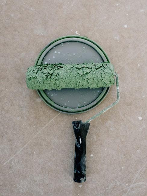 Eine Farbrolle mit grüner Wandfarbe fürs Streichen