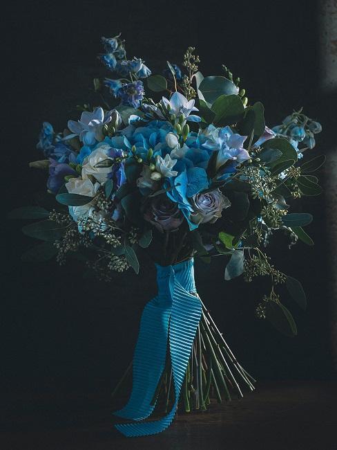 Blauer Blumenstrauß vor schwarzem Hintergrund