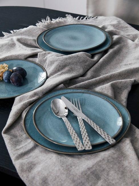 Blaues Geschirr auf grauer Tischdecke