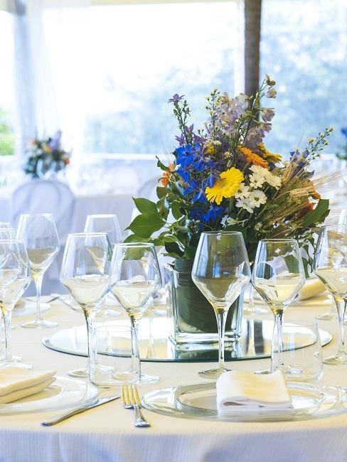Tischdeko mit einem Strauß mit blauen und gelben Blüten