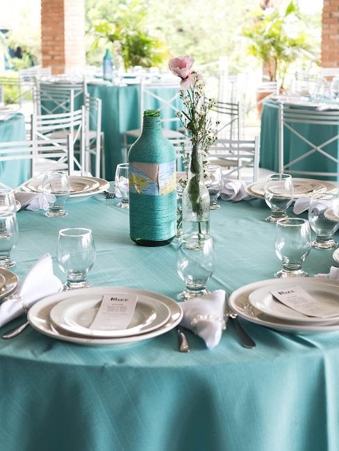 Türkisfarbene Tischdeko auf einem runden Tisch