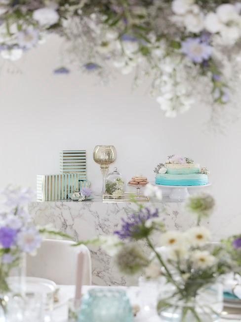 Tisch mit Geschenken und blauen Blumen